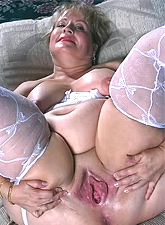 Blonde sugar mommy with giant boobs is on her knees posing